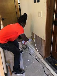 Technician Repairing Water Damaged Drywall